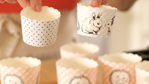 A person holding cupcake liners showing the design