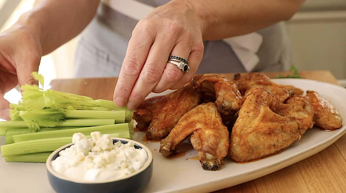 A person placing celery on a platter with buffalo wings and blue cheese dressing