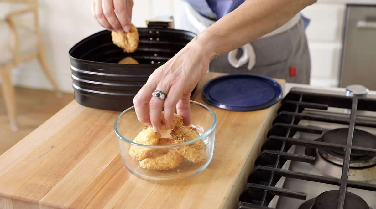 a person placing air fried shrimp in a container for storage
