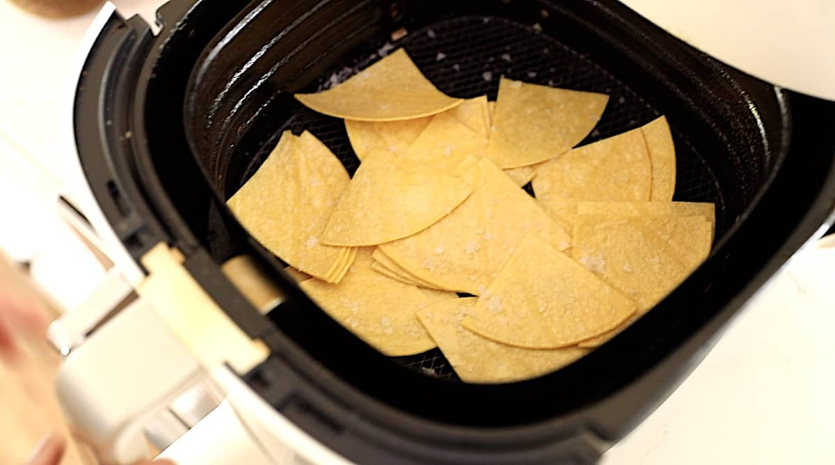 Corn tortillas in the air fryer basket about to be air fried