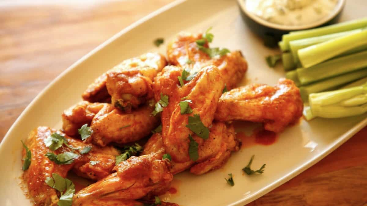 a plate of air fryer chicken wings with buffalo sauce, blue cheese dressing and celery
