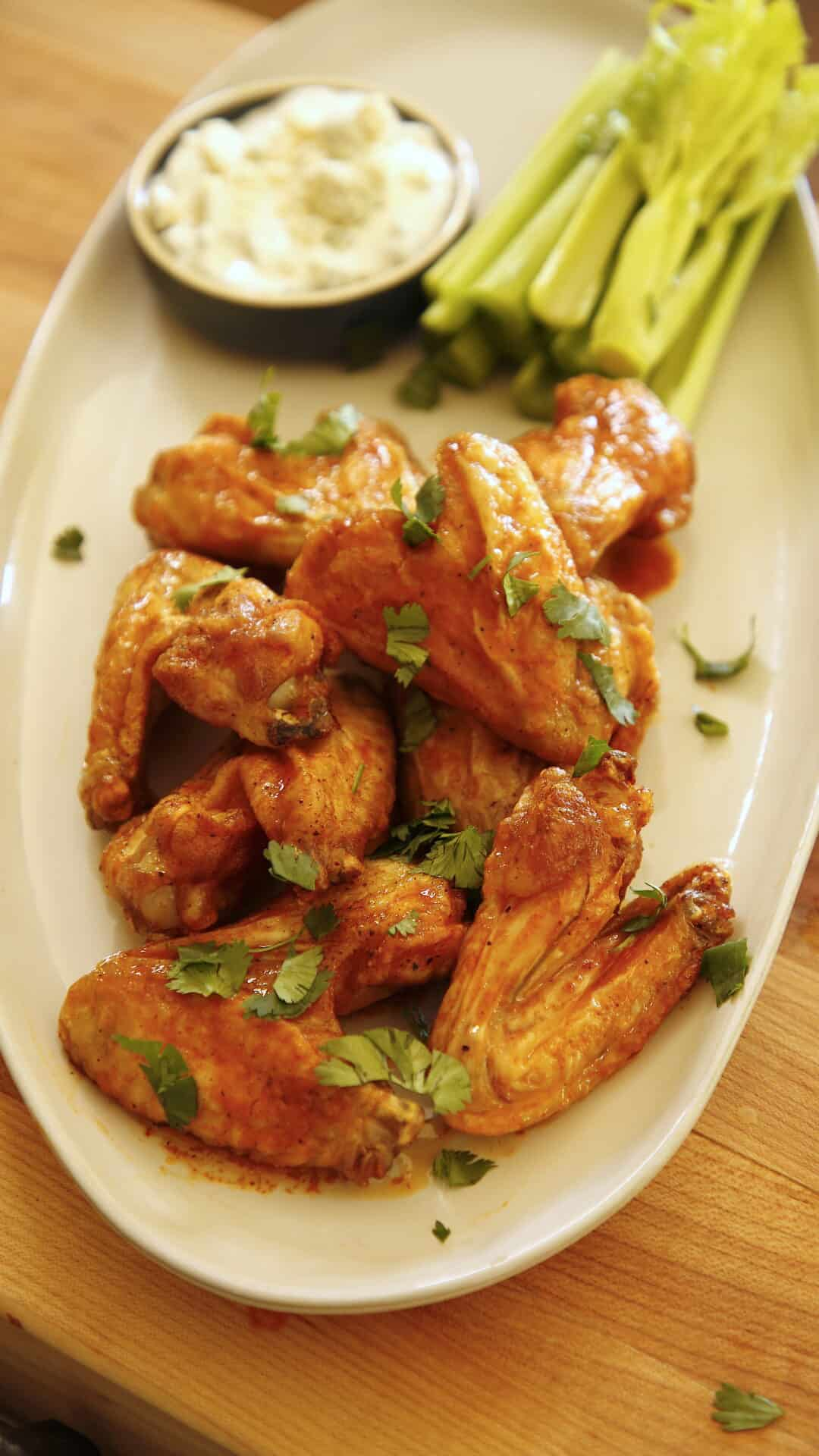 a vertical image of air fryer chicken wings loaded with buffalo hot sauce on an oval platter