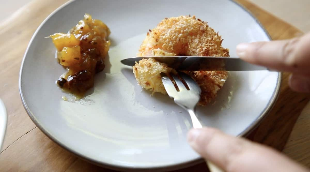a person cutting into an air fried coconut shrimp on a plate with a fork