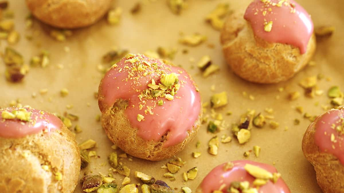 Creame puffs dipped in raspberry icing and topped with pistachios