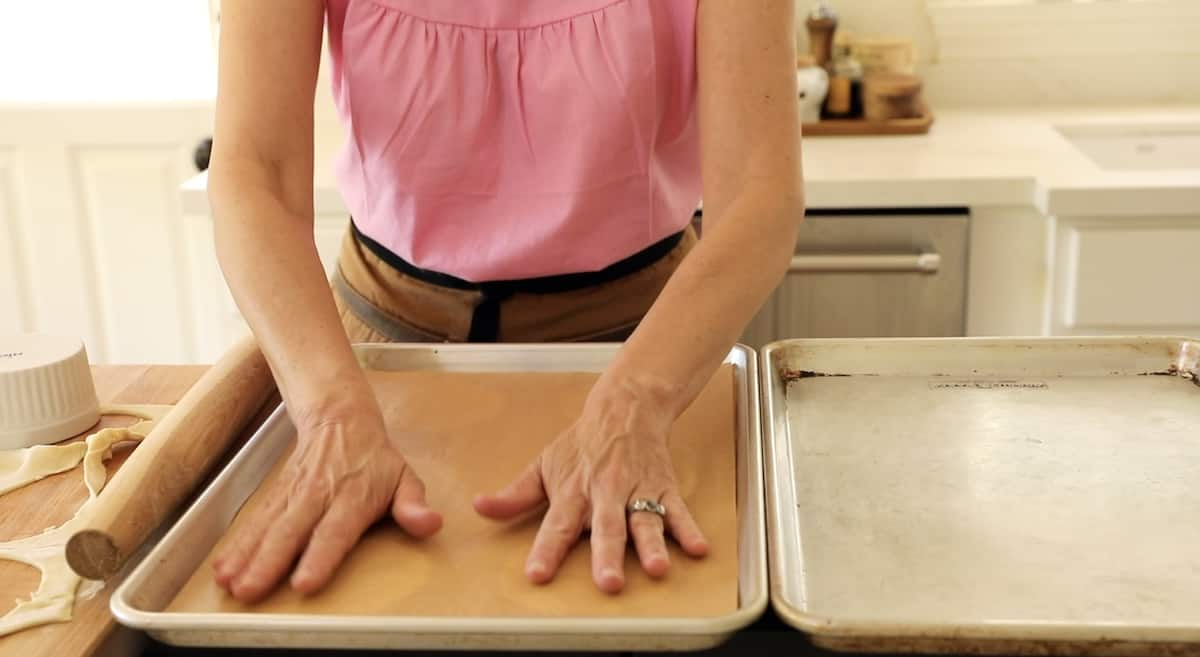 a person placing parchment paper on top of puff pastry rounds