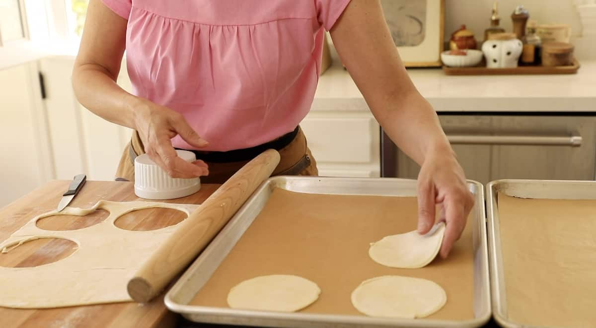 a person placing puff pastry rounds on a sheet pan