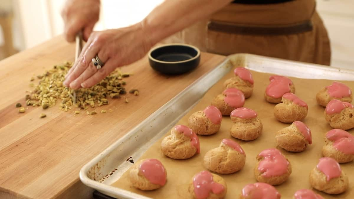 Cream puffs dipped in raspberry icing on a tray with a person chopping pistachios in the background