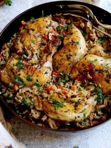 One Pot Chicken and Rice on a counter with silver serving pieces